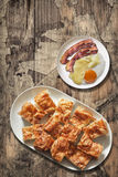 Plateful of Gibanica Crumpled Cheese Pie with Plate of Fried Egg and Bacon Rashers Set on Old Wood Background Royalty Free Stock Image