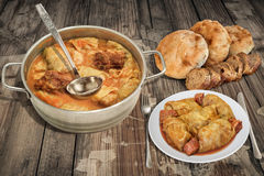 Plateful Of Pickled Cabbage Stuffed Rolls Cooked With Smoked Pork Ribs And Leavened Pitta Flatbread Served On Old Garden Table. Traditional Serbian gourmet dish Stock Image