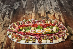 Plateful Of Traditional Serbian Appetizer Dish Meze Set On Old Weathered Cracked Flaky Garden Table Surface. Plateful of traditional Serbian gourmet savory stock photo