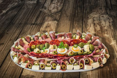 Plateful of Serbian Appetizer Meze on very old Wooden Table Royalty Free Stock Image