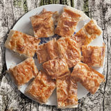 Serbian Traditional Crumpled Cheese Pie Gibanica Slices Served On White Porcelain Plate Set On Old Weathered Cracked Wood Surface. Crumpled cheese pie Gibanica Stock Photography