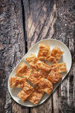 Plateful Of Serbian Traditional Crumpled Cheese Pie Gibanica Set on Old Weathered Cracked Grooved Wooden Garden Table. Plateful of Serbian traditional crumpled Stock Photo