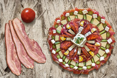 Plateful of Serbian Traditional Savory Appetizer Meze with Three Bacon Rashers and Tomato Alongside on Chipboard Background Royalty Free Stock Image