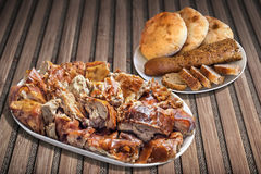 Plateful of Spit Roasted Pork with Sliced Baguette and Pita Bread Loafs on Bamboo Place Mat Stock Photos