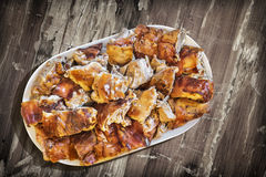 Plateful of Spit Roasted Pork Slices on Old Lacquered Cracked Peeled-off Wooden Garden Table Royalty Free Stock Photography