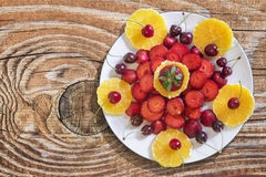 Strawberries And Cherries With Orange Slices Served On White Porcelain Plate Set On Old Wooden Knotted Pine Wood Table Surface. Strawberries and Cherries with royalty free stock image
