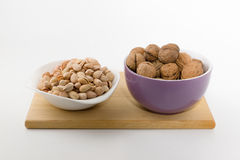 Platefuls of different nuts stand on a plate on a white backgrou Stock Image