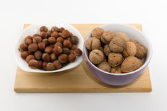 Platefuls of different nuts stand on a plate on a white backgrou Royalty Free Stock Photos