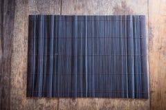 Platemat de bambú en fondo de madera Fotos de archivo