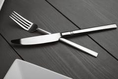 Platen en bestek op een houten lijst Geplaatst bestek: vork, lepel en mes Royalty-vrije Stock Afbeelding