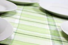 Platen op tafelkleed in keuken stock fotografie