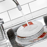Plates. Under the water jet of a kitchen sink Royalty Free Stock Image