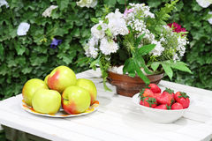 Plates with apples, strawberries and flowers Royalty Free Stock Images