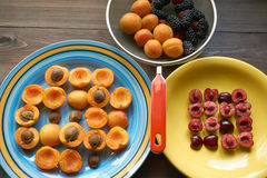 Plates with apricots and cherries and colander full of berries Royalty Free Stock Photo