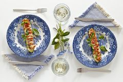 Plates with baked courgette with tomatoes and cheese. Glasses with white wine, romantic dinner for two. Homey atmosphere clean white table. Top view Stock Photography