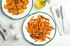 Plates with baked sweet potato slices served on table. Top view royalty free stock images