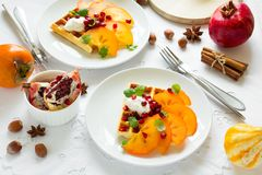 Plates of Belgian waffles with persimmon, pomegranate seeds and sour cream royalty free stock photos