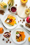 Plates of Belgian waffles with persimmon, pomegranate seeds and sour cream royalty free stock images