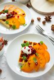 Plates of Belgian waffles with persimmon, pomegranate seeds and sour cream royalty free stock photo