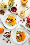 Plates of Belgian waffles with persimmon, pomegranate seeds and sour cream stock photo