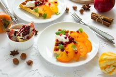 Plates of Belgian waffles with persimmon, pomegranate seeds and sour cream stock photography