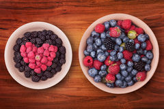 Plates with berries on the wooden table Royalty Free Stock Image