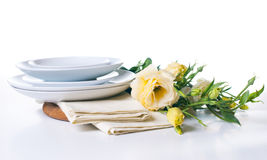 Plates and a bouquet of yellow flowers Stock Photo