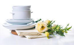 Plates and a bouquet of yellow flowers Royalty Free Stock Photos