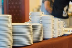 Plates and bowls, white ceramic on a brown tablecloth. Royalty Free Stock Photo