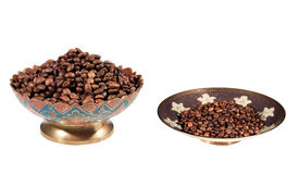 Plates of coffee. Coffee beans on traditional decorated indian plates isolated on white background Stock Image