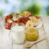Plates with cookies, cup with milk and honey Stock Photo