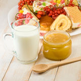 Plates with cookies, cup with milk and honey Royalty Free Stock Images