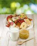 Plates with cookies, cup with milk and honey on the table on a green background Stock Photos