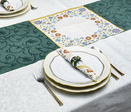 Plates, cutlery, napkin in the napkin ring, tablecloth. Selective focus. Table is set. Plates, cutlery, napkin in the napkin ring, tablecloth. Selective focus Stock Images