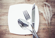Plates and cutlery on a wooden table Stock Photos