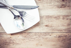 Plates and cutlery on a wooden table Stock Images