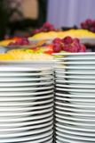 Plates and different fruits. Behind Royalty Free Stock Image