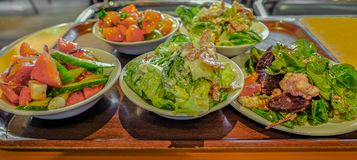 Plates of different salads on a wooden looking tray. stock photo