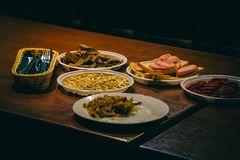 Plates with food on the table. In a dark room Royalty Free Stock Photo