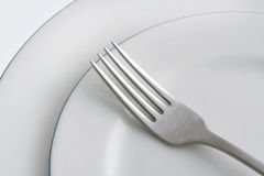Plates and Fork. Two blue-rimmed white plates, with silver fork stock photography