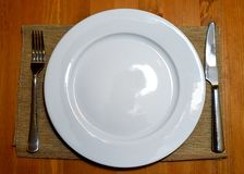 Plates with a fork, spoon and a knife on table Stock Images
