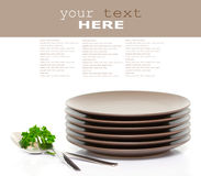 Plates, fork, spoon and parsley. Stack of brown round plates with fork, spoon and parsley (with sample text Royalty Free Stock Image