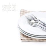 Plates, forks - utensils for serving on napkin. Plates and forks - utensils for serving on napkin, isolated on white Royalty Free Stock Image