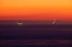Plates-formes pétrolières dans l'océan de coucher du soleil Image libre de droits