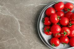 Plates with fresh ripe tomatoes. On grey background, top view Stock Photos