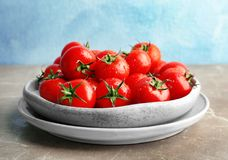 Plates with fresh ripe tomatoes. On table Stock Photos
