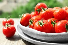 Plates with fresh ripe tomatoes. On table outdoors Stock Images