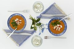 Plates and glasses, romantic dinner for two. Orange soup. Plates and glasses, romantic dinner for two. Homey atmosphere clean white table. Top view. Orange soup Stock Image