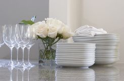 Plates, glasses & roses on the counter. Plates, glasses & roses on counter for dining Stock Photo