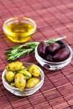 Plates of green olives, black olives and olive oil on bamboo nap Stock Photos